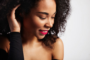 profile portrait of black woman with curly hair watching aside