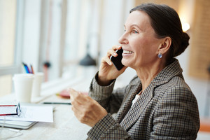 Profile view of cheerful senior woman talking to her friend on smartphone while enjoying coffee break in lovely cafe with panoramic windows, head and shoulders portrait