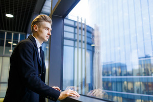 Profile view of handsome young businessman looking out panoramic window thoughtfully while standing in spacious office lobby, waist-up portrait