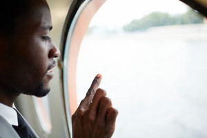 Profile view of pensive African American man enjoying picturesque view from window of ship cabin, head and shoulders portrait