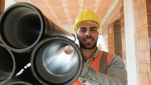 Proud people working in construction site. Portrait of happy white man at work in new house. Professional latino worker carrying pipes and smiling at camera