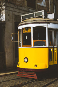 Quaint yellow tram on the rails of old and beautiful street of Alfama District of Lisbon. City touristic landmarks of Lisboa Lissabon