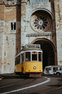 Quaint yellow tram passes directly in front of the Se Cathedral in Lisbon. Lisboa Lissabon