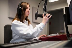 Radio Jockey Adjusting Microphone While Wearing Headphones In St