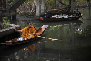 ratchaburi thailand - january11,2019 : thai monk sailing wood boat in narrow canal on dumneon saduak district in ratchaburi for recieving food in early morning