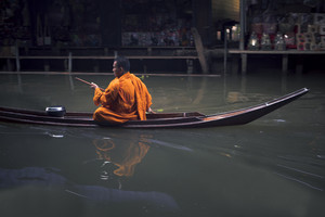 ratchaburi thailand - january1,2019 : thai monk sailing boat in dumneonsaduak canal ,floating market one of most popular traveling destination in  ratchaburi thailand