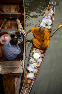 ratchaburi thailand - january12,2019 : thai monk receiving food from thai woman offering in dumneon saduak canal one of most popular traveling destination in thailand
