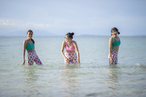 RAYONG THAILAND - MAY2,2018 : three asian woman wearing yoga suit standing in sea water and laughing with happiness emotion