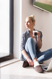 Real Woman Using laptop At Home on the floor Drinking Coffee Enjoying Relaxing