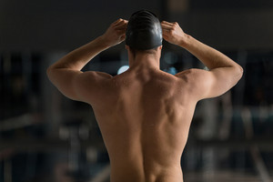 Rear view of a male swimmer adjusting his swimming goggles