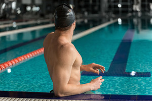 Rear view of a male swimmer standing at the edge of a swimming pool