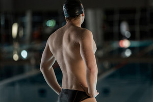 Rear view of a male swimmer with his hands on his hips