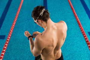 Rear view of a man adjusting his watch infront of a swimming pool