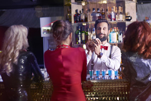 Rear view of bartender preparing cocktail for pretty women