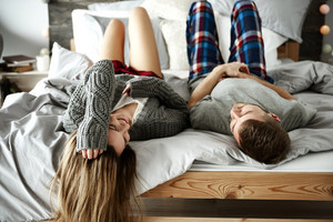 Rear view of cheerful couple lying down on bed