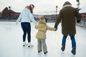 Rear view of mother, father and daughter skating at leisure