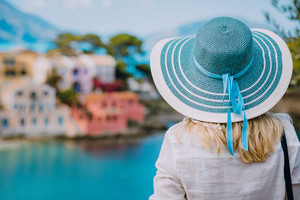 Rear view of tourist woman wear blue sunhat and white clothes admire view of colorful tranquil colorful houses of Assos village on sunny day. Visiting Kefalonia in summer. Travel vacation in Greece