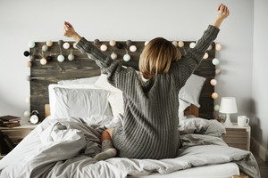 Rear view of woman stretching in her bed