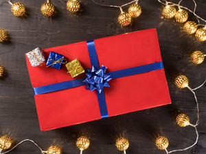 Red christmas gift box with smaller gift boxes on dark wooden floor surrounded by golden lights. Happy atmosphere
