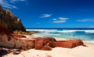 Red coloured rocks on pristine beach