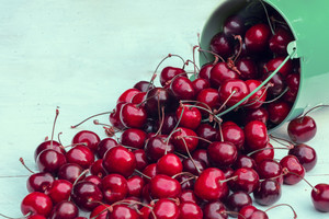 Red fresh sweet cherries in a bucket on wooden grunge table