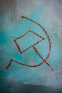 Red hammer and sickle painted on a blue colored wall. Vertical orientation