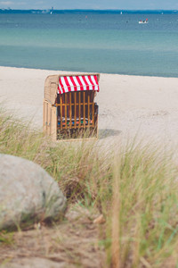 Red roofed chair on sandy beach in Travemunde, North Germany