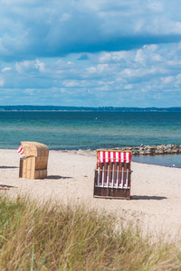 Red striped roofed chairs on empty sandy beach in Travemunde. Grass bush in foreground. Germany
