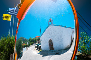 Reflection of small greek chapel in the traffic safety mirror.
