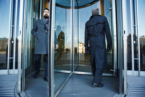 Revolving door with elegant businessmen inside