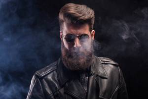 Rich handsome bearded man with sunglasses and leather jacket over black background. Attractive man.