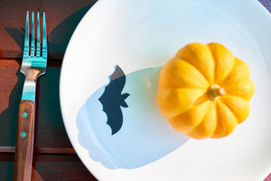 Ripe pumpkin on plate with black paper bat and fork near by