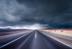 Road leading into a desert storm
