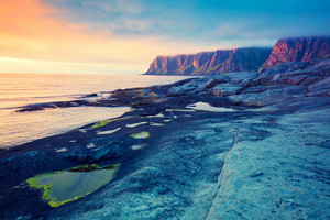 Rocky beach at magic pink blue sunset, wild nature Norway. Senja island. Beautiful bay. Picturesque sunset