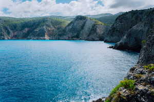 Rocky cliff landscape of coastline with cypress trees on the plateau. Mediterranean sea