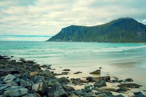 Rocky sandy beach Skagsanden with mountain at Lofoten islands, Norway