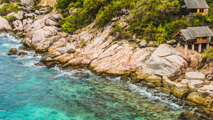 Rocky south costline of Koh Tao Islands with bungalows on granite rocks. Thailand