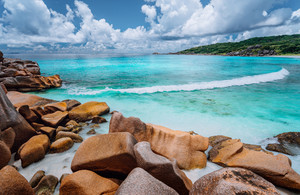 Rolling wave and stunning granite formations on the beautiful tropical island with white clouds of La Digue, Seychelles