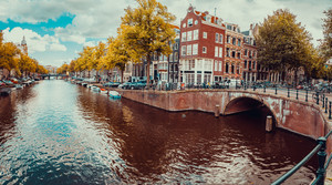 Romantic Amsterdam canals with bridges, boats and typical Dutch houses. Holland, Netherlands. Cityscape in terracotta colors