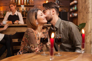 Romantic couple dating in a vintage restaurant. Handsome man kissing gently his girlfriend cheek