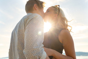 Romantic couple kissing on beach against the sun