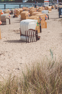 Roofed wooden chairs on sandy sea beach. German travel. Travemunde, Germany