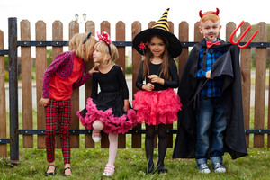 Row of Halloween kids standing against fence