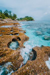 Rugged coastline of paradise beach with granite rocks and blue crystal clear water on a rough coast of Anse Bazarca, Seychelles