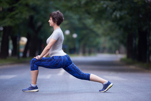 runner   woman warming up and stretching before morning jogging