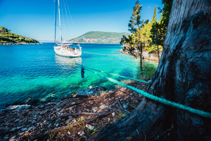 Sail boat docked alone in emerald hidden lagoon among picturesque mediterranean nature Ionian Islands, Greece