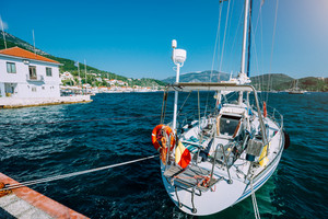 Sailing boat moored up in the picturesque Greek town. Mediterranean landscape of green hills, mountains and clear water