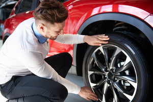 Salesman checking the shiny rims in new car