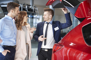 Salesman showing couple the car trunk