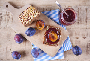 Sandwich with fresh plum jam and plum on cutting board